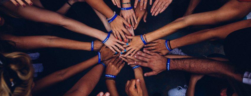 Zu sehen sind viele Hände/Arme, die als Team zusammenhalten.