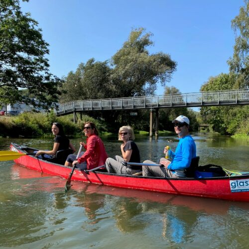 Das Bild zeigt eines der vier Kanus mit Kollegen des techmatrix Teams während einer Kanufahrt.